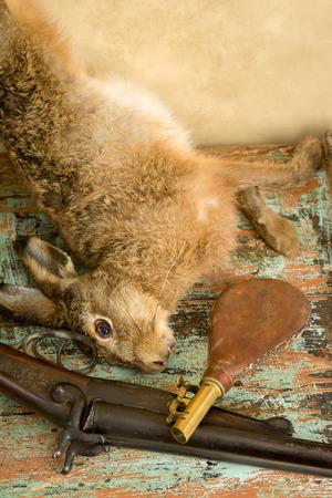 gunpowder: Old hunting scene with dead hare, rifle and leather gunpowder pouch