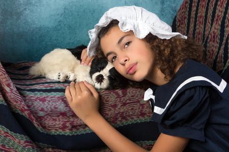 Süßes viktorianisches Mädchen im alten Stil mit ihrem Hund posiert