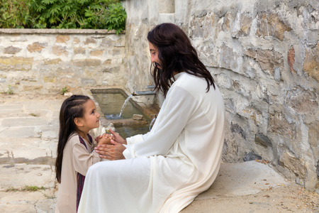Biblical scene when Jesus says, let the little children come to me, blessing a little girl. Historical reenactment at an old water well. Archivio Fotografico