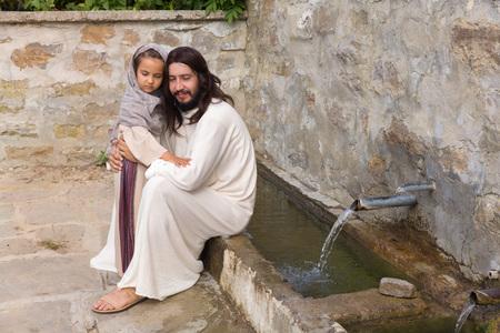 Scène biblique quand Jésus dit, laisser les enfants venir à moi, bénissant une petite fille. Reconstitution historique à un vieux puits d'eau.