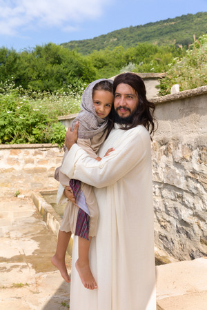Biblical scene when Jesus says, let the little children come to me, blessing a little girl. Historical reenactment at an old water well. Stock Photo