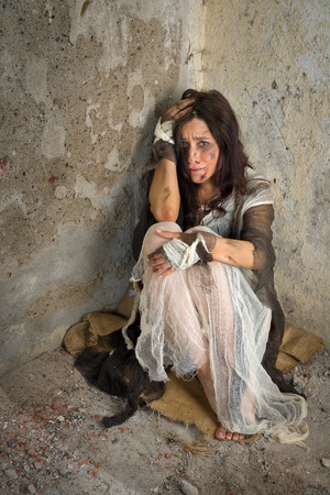 intimidated: Abused and frightened woman sitting in the corner of a derelict building