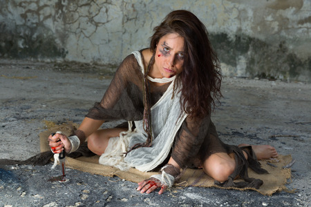 intimidated: Dangerous woman in rags sitting in a derelict building with a bloody knife Stock Photo