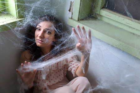 fear woman: Young scared woman trapped in a corner with cobwebs or spiderwebs Stock Photo