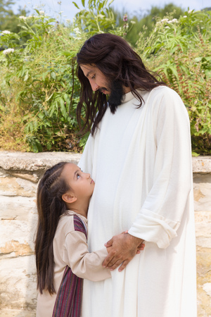 jesus: Biblical scene when Jesus says, let the little children come to me, blessing a little girl. Historical reenactment at an old water well. Stock Photo