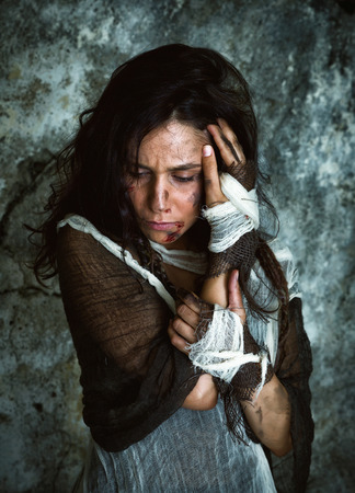 abused women: Homeless young woman dressed in rags in a derelict building