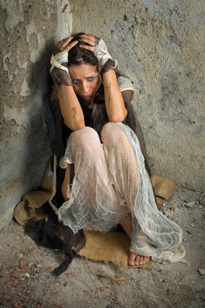 Abused and frightened woman sitting in the corner of a derelict building