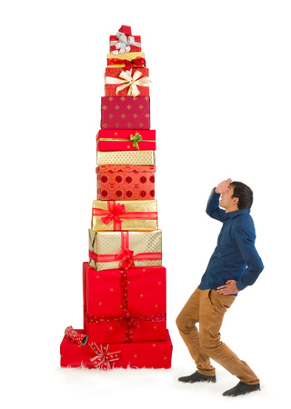 Funny scene of a young man looking up to a huge pile of christmas presents photo