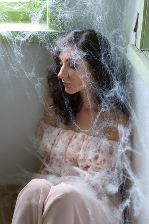 cobwebs: Young scared woman trapped in a corner with cobwebs or spiderwebs Stock Photo