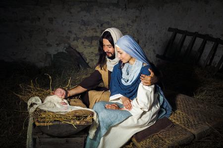 Leef Kerstmis kerststal in een oude schuur - Re-enactment spelen met authentieke kostuums. De baby is een (eigendom uitgebracht) pop. Stockfoto - 64485515