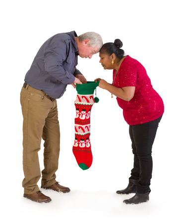 funny guys: Mature mixed race couple looking into a christmas stocking