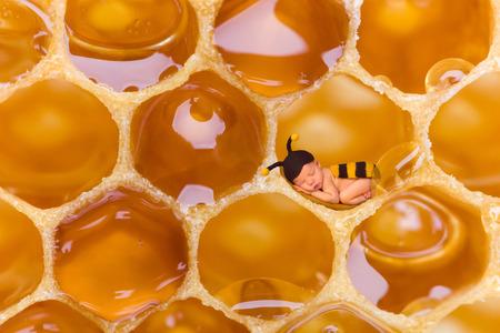 Pasgeboren baby in bee outfit slapen in een echte honingraat