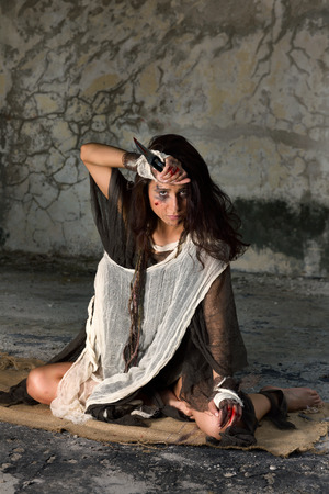 innocense: Scared young woman in rags sitting in derelict building wounded, abused and bleeding