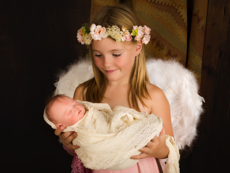 swaddle: Pink little girl playing an angel in a Christmas nativity scene with a doll