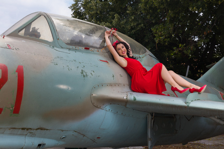 flashy: Sexy pin-up model in flashy red dress posing on a wing of a WW2 airplane