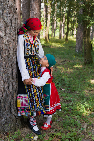 Young mother posing with her little girl in traditional Bulgarian costume