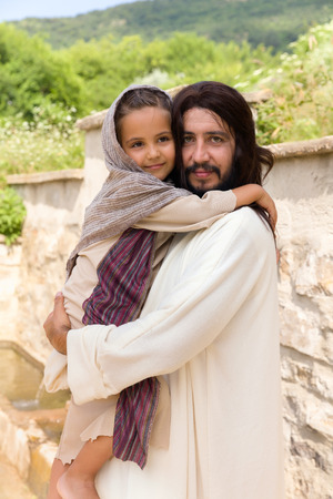 blessing: Biblical scene when Jesus says, let the little children come to me, blessing a little girl. Historical reenactment at an old water well. Stock Photo