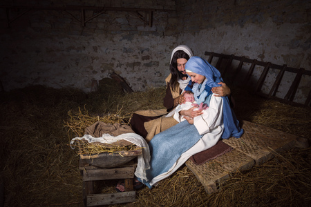 christmas scene: Live Christmas nativity scene in an old barn - Reenactment play with authentic costumes.  The baby is a (property released) doll.