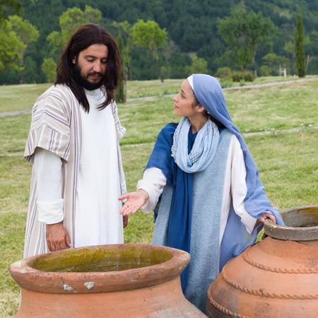 Riproduci scena biblica del miracolo della trasformazione dell'acqua in vino - Madre Maria dice a Gesù non c'è più vino sinistra Archivio Fotografico