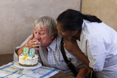 pensioner: Naughty old pensioner lighting his cigarette on his birthday cake