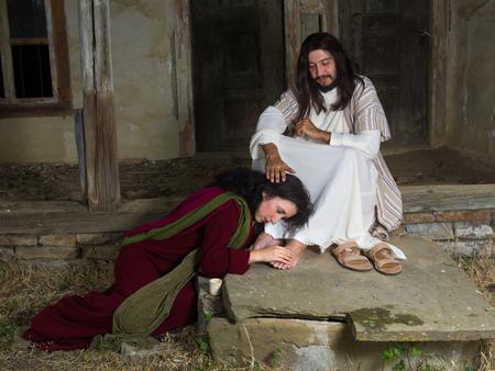 arrepentimiento: María Magdalena llorando de vergüenza y embalsamar los pies de Jesús Foto de archivo
