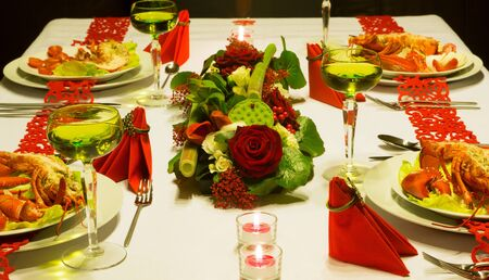 restaurant dining: Luxury lobster and white wine on a festive table with red folded napkins Stock Photo