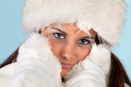 Winter girl with white fur hat wearing warm fur hat photo