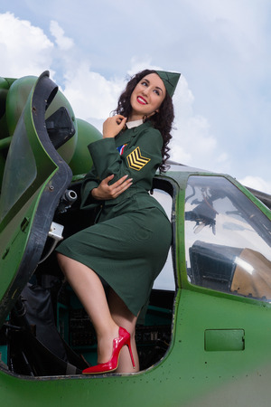Happy pin-up model in WW2 uniform posing in an old-timer helicopter Stock Photo
