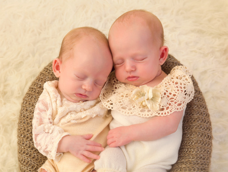 identical: Three weeks old newborn identical twin babies dressed in lace