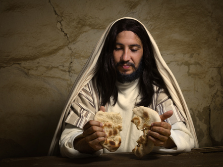 Authentic reenactment scene of Jesus breaking the bread during Last Supper, saying this is my body. Stock Photo