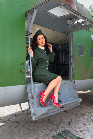 reenactment: Sexy pin-up model in WW2 uniform posing against old-timer aircraft Stock Photo