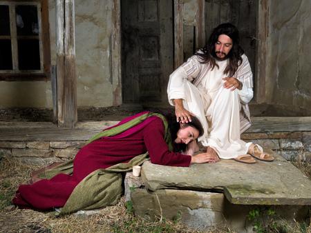 María Magdalena llorando de vergüenza y embalsamar los pies de Jesús Foto de archivo