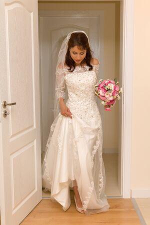 matrimonio feliz: Preciosa joven novia entrando en la habitación con su vestido de boda tradicional