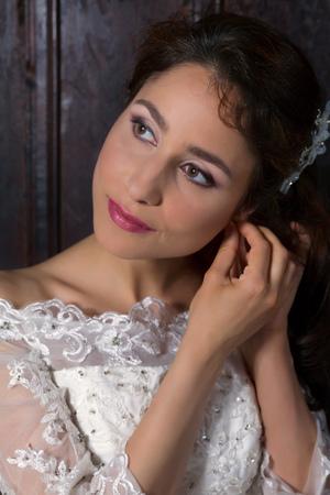 Georgeous brunette bride posing indoors in her wedding dress Stock Photo