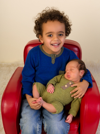 Proud African toddler presenting his newborn baby brother Stock Photo
