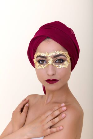 Beautiful model with gold leaf make-up and red head scarf