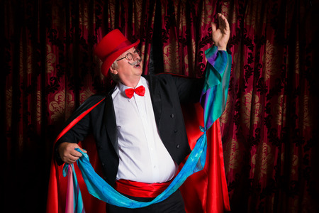 hanky: Funny senior magician performer doing magic tricks on stage
