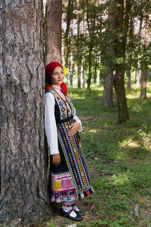젊은 여자가 전통적인 불가리아어 의상을 입고 포즈