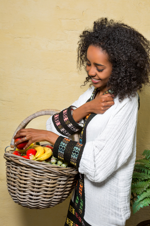 ethiopian ethnicity: Young Ethiopian girl with fruit basket wearing a white traditional dress