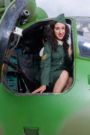 Happy pin-up model in WW2 uniform posing in an old-timer helicopter photo
