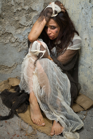 Abused and frightened woman sitting in a corner of a derelict building