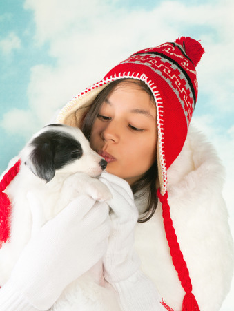 Girl in winter coat holding a 5 weeks old border collie puppy