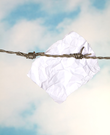 Blank note or message hanging on barbed wire Stock Photo