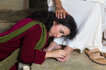 Mary Magdalene crying of shame and embalming Jesus' feet Foto de archivo