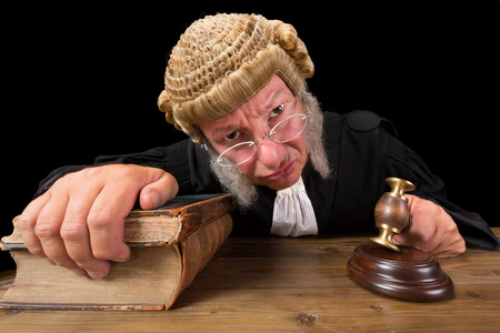 Angry judge in extreme wide angle closeup with hammer and wig Stock Photo