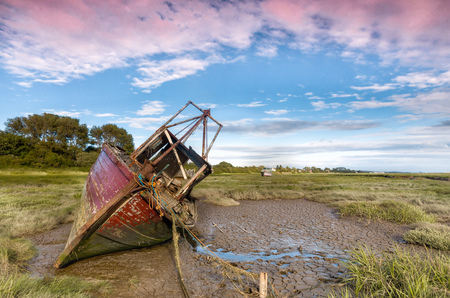 Derelict fishing boat wrecks lying in the mud flats on the riverbanks at Heswall near Liverpool Stock Photo