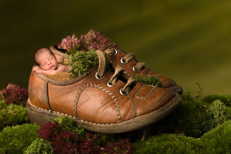 Newborn baby sleeping in old children shoes