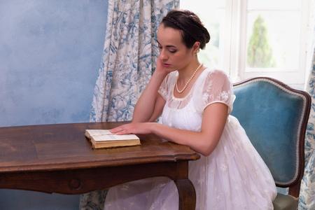 Bella giovane donna in autentico abito regency che legge un libro in una stanza vintage Archivio Fotografico