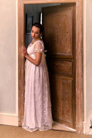Giovane donna in autentico abito regency in piedi su una porta