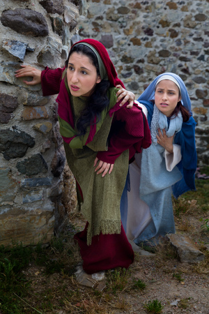 Mother Mary and Mary Magdalene standing at the entrance of the empty tomb of Jesus on Easter morning Stock Photo